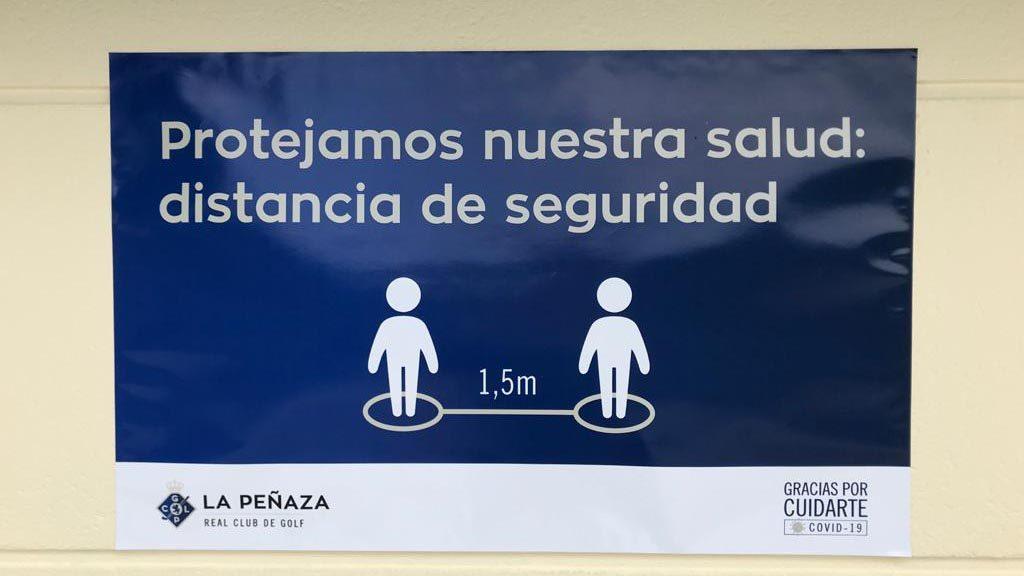 Cartel que recuerda la importancia de la distancia de seguridad en La Peñaza con la reapertura del campo de golf